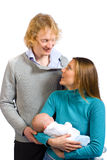 Happy family. Two first time parents holding their newborn baby and looking at each other affectionately Stock Photography