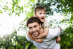 Happy family. The son embraces the daddy for a neck against the sky and foliage of trees Stock Photos