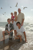 Happy Family. A family portrait. An american family on the shore of a beach with seagulls behind them stock photos