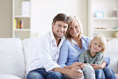 Happy Family. Young family with a child on the couch in the apartment Royalty Free Stock Images