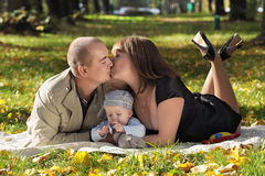 Happy family. The family lies on a grass in park and kiss Stock Image