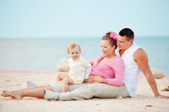 Happy family. Portrait ofl young happy parents with child at the beach Stock Photos