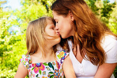 Happy Family. Little girl giving mother a big kiss Stock Image