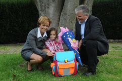 Happy family. Little girl posing wiih her parents at her first school day. She got a large cornet filled with sweets and little presents given to children  in Stock Photography