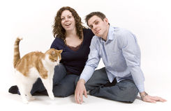 Happy Family. Young couple spends time playing with their pet cat royalty free stock image