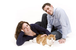 Happy Family. Young couple spends time playing with their pet cat royalty free stock photo