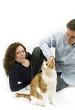 Happy Family. Young couple spends time playing with their pet cat royalty free stock images