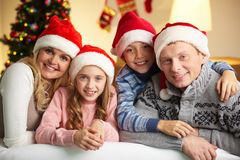 Happy family. Portrait of four happy family members in Santa caps looking at camera with smiles Royalty Free Stock Photo