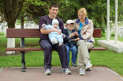 Happy Family. Family sits on bench in a park stock photography