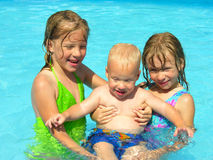 Happy family. Two sisters hold their one year old brother in the swimming pool Royalty Free Stock Photos