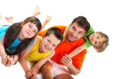 Happy family. A man poses with three happy children. They are dressed in colourful clothes and smiling Royalty Free Stock Image
