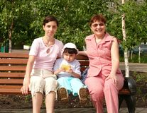 Happy family. Three women in different ages sitting on bench Royalty Free Stock Images