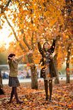 Happy family. Vertical photo,  happy beautiful little girl with mather throw up  autumnal leafage, in park. Focus on little girl Royalty Free Stock Images
