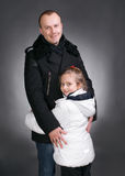 Happy family. Smiling father and daughter in winter outwear on a gray background Royalty Free Stock Images