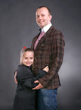 Happy family. Smiling higging father and daughter both in suits on a gray background stock photos