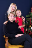 Happy family. Under christmas tree on dark blue background Stock Photography