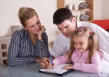Happy family. Mother and father helping their daughter with homework, family at home royalty free stock photos