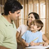 Happy family. Hispanic parents making eye contact with son doing homework Royalty Free Stock Photography