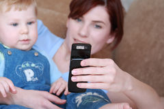 Happy family. Young mum with the small beautiful boy together look at a mobile phone Stock Image