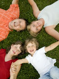 Happy family. Parents with kids laying on the grass Royalty Free Stock Image
