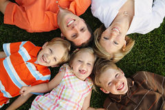 Happy Family. Young caucasian family lying on grass together and looking upward with big smiles Stock Photos
