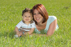 Happy Family. Beautiful mother lying in grass smiling with son Royalty Free Stock Images
