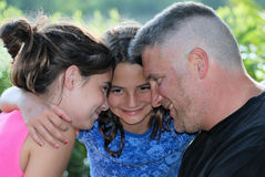 Happy Family. A father and his daughters having fun together and gazing into each others' eyes Stock Images