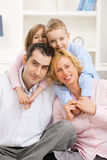 Happy family. At home with daugther and son, smiling. Children hugging their parents from behind stock photography