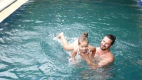 Happy family, active father with little child, adorable toddler daughter, having fun in swimming pool. stock video
