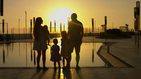 Happy family admiring the sunset by the pool. Happy family with kids admiring the sunset by the pool. Parents kissing each other Stock Photography