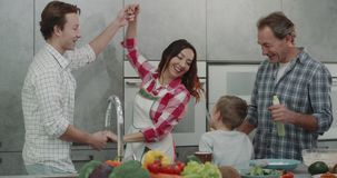 Happy family adult parents and two boy have a nice weekend together in the kitchen making breakfast and dancing same stock video