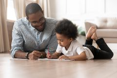 Happy family african dad and cute kid boy drawing together. Happy family african dad and cute little kid boy drawing together, loving black father help teach royalty free stock photography