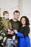 Happy family with against decorating Christmas tree Royalty Free Stock Photos