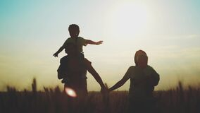 happy family in the agricultural park. silhouette of a friendly family of farmers sunset walking in a wheat field