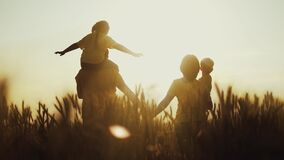 happy family in the agricultural park. silhouette of a friendly family of farmers walking in a wheat field. agriculture