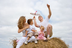 Happy family with aircraft on haystack summertime Royalty Free Stock Image