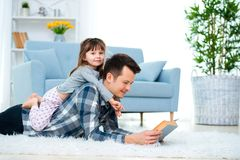 Happy Family And Father`s Day Concept. Dad With Daughter Spending Time Togetherness At Home. Cute Little Girl On Dad`s Back Lyin Stock Photography