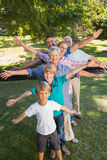 Happy family with arms outstretched in the park Stock Photography