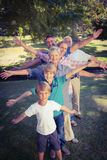 Happy family with arms outstretched in the park Stock Photo