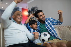Happy family with arms raised watching soccer match Stock Image