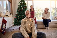 Happy family arranging the christmas lights and having fun. Happy family at home during christmas. Little girl with christmas lights around her grandfather while Royalty Free Stock Photo