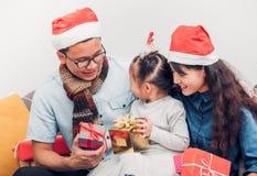 Happy family Asia family wear santa claus hat exchange Christmas Stock Photos