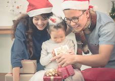 Happy family Asia family wear santa claus hat unwrap Christmas g. Ift box at house xmas party,Holiday celebrating festive concept,vintage filter Stock Photo