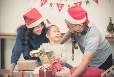 Happy family Asia family wear santa claus hat unwrap Christmas g Stock Images