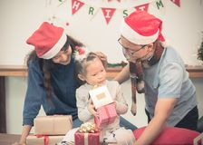 Happy family Asia family wear santa claus hat unwrap Christmas g Royalty Free Stock Photo