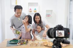 Happy family asian making a Vlog video blogger digital camera with cooking. In the kitchen room royalty free stock images