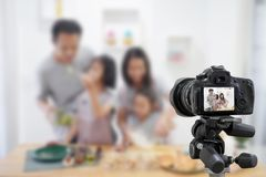 Happy family asian making a Vlog video blogger digital camera with cooking stock images