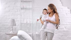 Happy family attractive young mother and cute baby having good time at white cozy interior. Medium long shot. Smiling adorable woman holding little kid feeling stock video