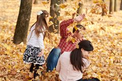 Happy family is in autumn city park. Children and parents. They posing, smiling, playing and having fun. Bright yellow trees royalty free stock images