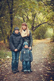 Happy family in autumn forest photo. Picture of beautiful women with sons standing in autumn forest royalty free stock image